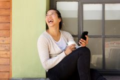 Portrait of happy asian woman sitting outside with a mobile phone Stock Photos