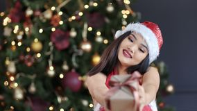 Portrait of happy Asian woman wearing Santa Claus hat and suit smiling and gives present in gift box. Congratulation Happy New Year. Pretty girl enjoying near