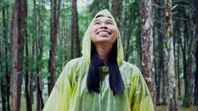 Portrait of Happy Asian woman wearing yellow raincoat stand in rain stock video