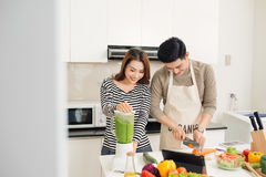 Portrait of happy asian young couple cooking together in the kit Stock Photography