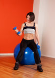 Portrait of happy athlete holding dumbbell. Portrait of happy brunette sitting on fitness ball with weights Stock Images