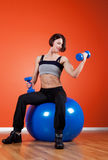 Portrait of happy athlete holding dumbbell. Portrait of athletic brunette with weights in gym Royalty Free Stock Image