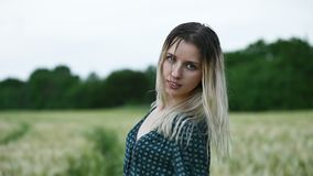 Portrait of a happy attractive Caucasian blonde girl with wet hair during a rain on the nature outdoor on a wheat field stock footage