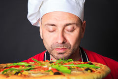 Portrait of happy attractive cook with a pizza Stock Images