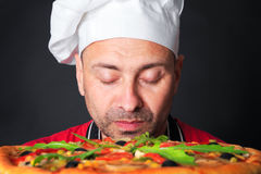 Portrait of happy attractive cook with a pizza Stock Photography