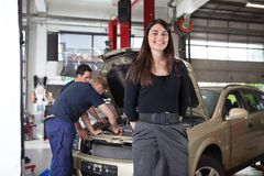 Portrait of Happy Attractive Female Customer. Portrait of attractive female in garage while people working in background Stock Photography