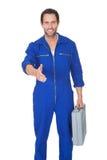 Portrait of happy automechanic offering handshake Royalty Free Stock Image