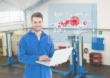 Portrait of happy automobile mechanic holding laptop and mechanic interface Stock Photography
