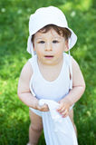 Portrait of happy baby boy wearing white hat, posing and looking into camera - outside, summer Royalty Free Stock Images
