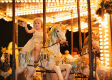 Portrait of happy baby girl riding on carousel Stock Photography