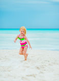 Portrait of happy baby girl running on beach Royalty Free Stock Image