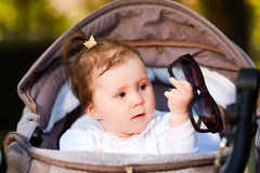 Portrait of the happy baby girl in a stroller in the city park at sunshiny day. Portrait of the happy baby girl in a stroller in the city park at warm sunshiny Stock Image