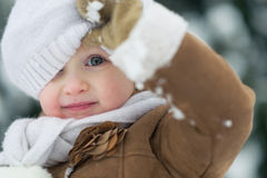 Portrait of happy baby looking out from hat in winter park stock image
