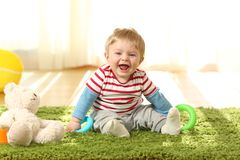 Portrait of a happy baby looking at you. Front view portrait of a happy baby laughing looking at you sitting on a carpet at home Royalty Free Stock Photography