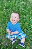 Portrait of happy baby sitting on the meadow. Portrait of happy baby age of 9 months sitting on the meadow Stock Image