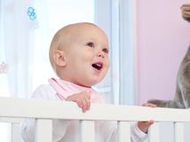 Portrait of a happy baby smiling in crib Royalty Free Stock Images