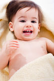 Portrait of a happy baby wrapped in yellow towel Stock Photos