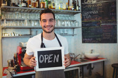 Portrait of happy barista holding chalkboard at cafe Stock Photo