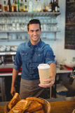 Portrait of happy barista offering coffee in disposable cup at cafe. Portrait of happy young male barista offering coffee in disposable cup at cafe Royalty Free Stock Image