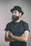 Portrait of happy bearded man with crossed arms looking away Stock Photo