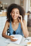 Portrait of happy beautiful african girl listening to music in headphones smiling sitting in cafe. Closed eyes. Copy space Royalty Free Stock Image