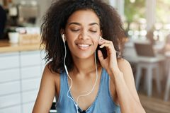 Portrait of happy beautiful african girl listening to music in headphones smiling sitting in cafe. Closed eyes. Copy space Stock Images