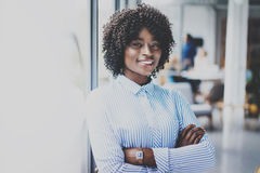 Portrait of happy beautiful african woman standing with arms folded and colleagues on background in modern loft. Businesswoman looking at the camera. Horizontal Royalty Free Stock Photo