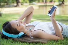Asian woman listen music at summer park. Portrait of happy beautiful Asian woman sleep and listen music on grass near water pond in summer park. Happy brunette Royalty Free Stock Image