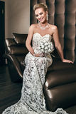 Portrait of a happy beautiful bride sitting on chair and holding Stock Image