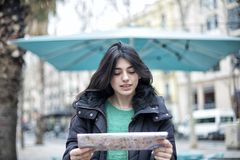 Portrait of happy beautiful casual woman traveler searching direction on location map. Young traveling female standing on the street and holding map royalty free stock images