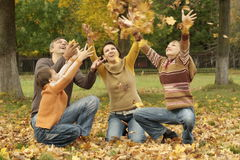 Beautiful family throw autumn leaves Royalty Free Stock Photo