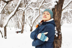 Portrait of happy beautiful girl leaned to the tree in winter Stock Photo