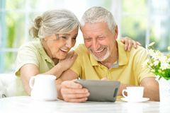 Portrait of happy beautiful senior couple using tablet royalty free stock photography