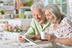 Portrait of happy beautiful senior couple using tablet Royalty Free Stock Image