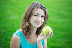 Portrait of happy beautiful woman with apple in park Royalty Free Stock Images