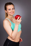 Portrait of  happy beautiful woman in fitness wear holding a red Stock Photography