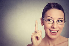 Portrait happy beautiful woman looking up pointing finger at blank copy space. Closeup portrait happy beautiful woman looking up pointing with finger at blank Royalty Free Stock Images