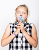 Portrait of happy beautiful young girl with sweet candys. pretty young girl dressed in a plaid shirt holding colorful Stock Images