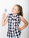 Portrait of happy beautiful young girl with sweet candys. pretty young girl dressed in a plaid shirt holding colorful Stock Photography