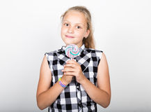 Portrait of happy beautiful young girl with sweet candys. pretty young girl dressed in a plaid shirt holding colorful Stock Image