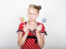 Portrait of happy beautiful young girl with sweet candys. pretty young woman dressed in a red dress with white polka Stock Photos
