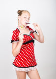 Portrait of happy beautiful young girl with sweet candys. pretty young woman dressed in a red dress with white polka Stock Photography
