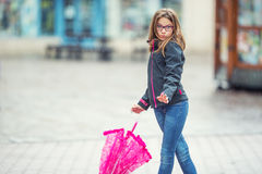 Portrait of happy beautiful young pre-teen girl with pink umbrella under rain Stock Photography