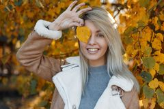 Portrait of a happy beautiful young woman with a bright yellow. Leaf outdoors in the autumn forest among the golden leaves on a sunny day. Charming fashionable royalty free stock photo