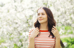 Portrait of happy beautiful young woman in flowering garden Royalty Free Stock Photo