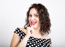 Portrait of happy beautiful young woman licking chupa chups. pretty woman with heart shaped lollipop Royalty Free Stock Photo