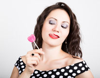 Portrait of happy beautiful young woman licking chupa chups. pretty woman with heart shaped lollipop Royalty Free Stock Photos