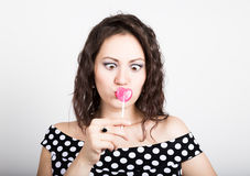 Portrait of happy beautiful young woman licking sweet candy and expressing different emotions. pretty woman with heart Stock Images