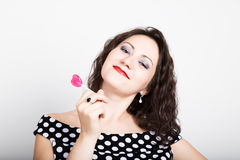 Portrait of happy beautiful young woman licking sweet candy and expressing different emotions. pretty woman with heart Royalty Free Stock Image