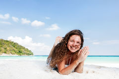 Portrait of a happy young woman posing while on the beach. Portrait of a happy beautiful young woman posing while on the beach Royalty Free Stock Images